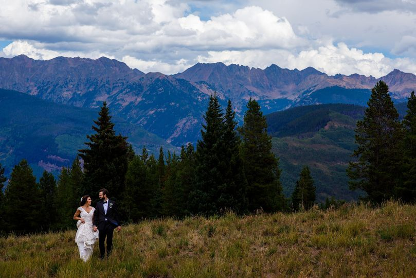 the bride and groom walk together atop vail mountain on their wedding day 51 377673