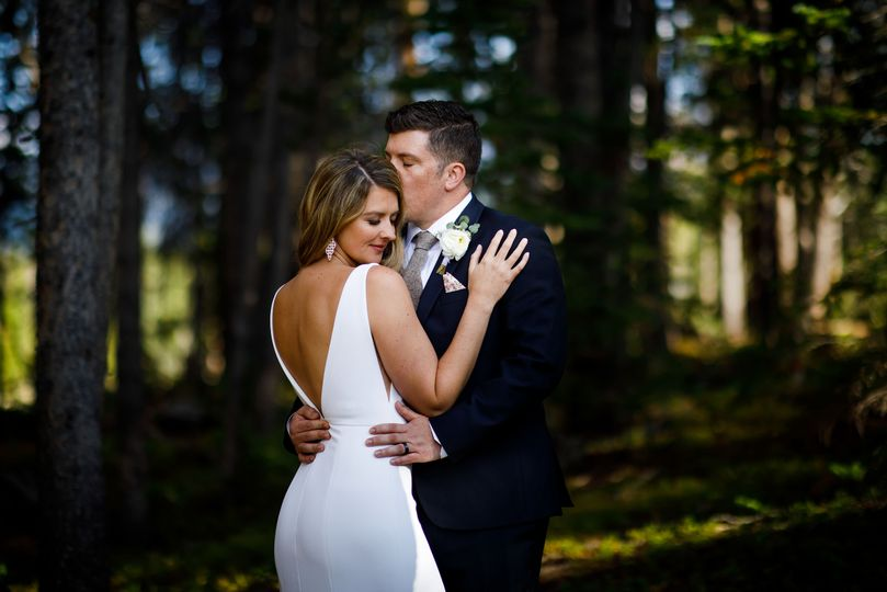 the bride poses while the groom gives her a kiss in a backless sexy gown during their wedding at tenmile station 51 377673