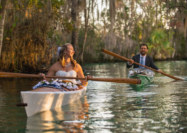 Bride and groom on kayaks