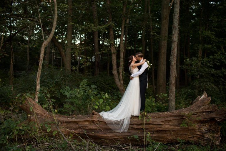 Newlyweds kissing in the woods