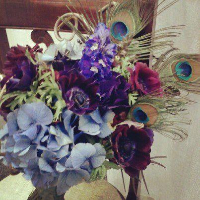 Peacock bouquet featuring antique blue hydrangea, purple anenomes, blue larkspur, burgundy snap...