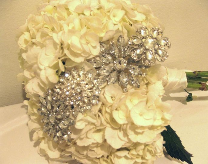 This chic design was created with white hydrangea and an asymmetrical stripe of rhinestone brooches.