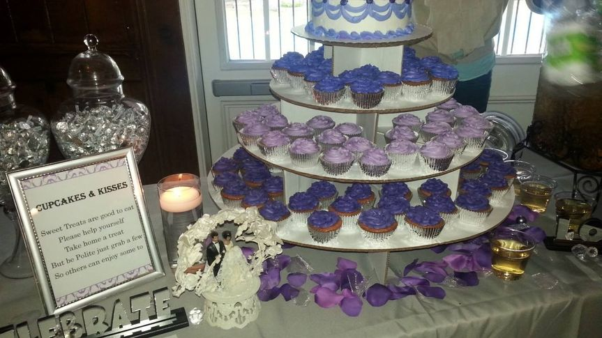 Dessert table with cupcake tower. Purple cupcakes, hersey kisses and top layer cake.
