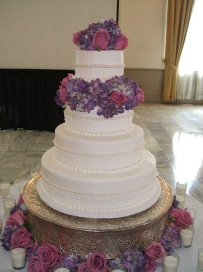 An elegant buttercream cake with edible pearl accents and cornelli lace trim.. Real flowers.  Venue...