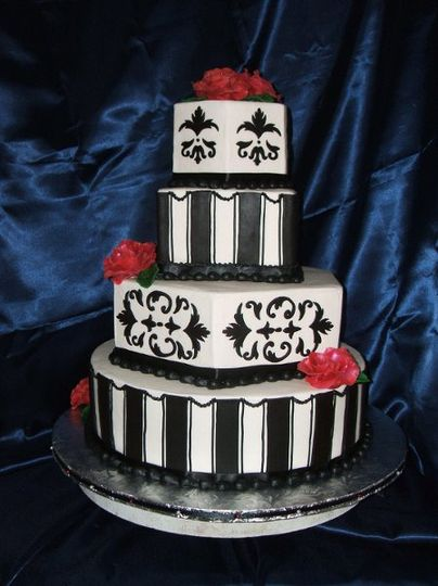An elegant buttercream cake with homemade chocolate fondant accents. Red chocolate roses adorn this...