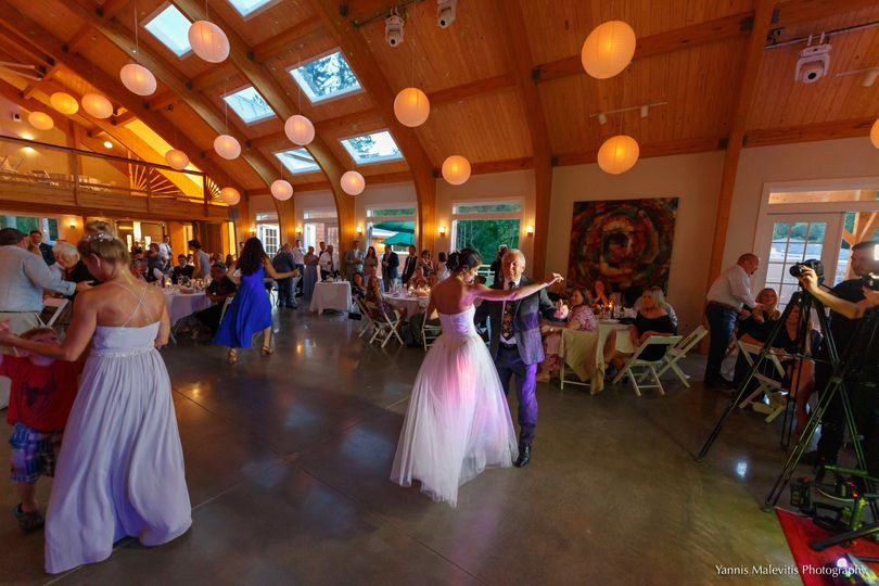 An enchanting bride and her father share a magical dance in the pavilion, surrounded by their loved...