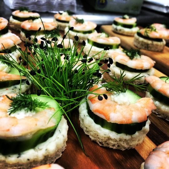 Sweet poached shrimp and cucumber canapés finished with dill butter and local micro herbs
