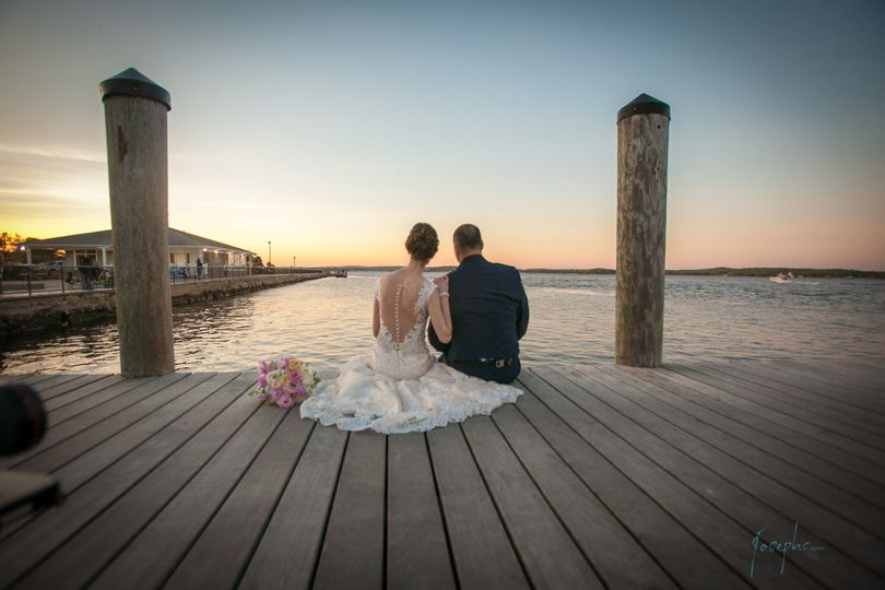 175c4702ae8c5526 1514488025475 bride and groom sitting on docks at sunset farth