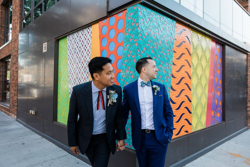 Two grooms against a wall of color