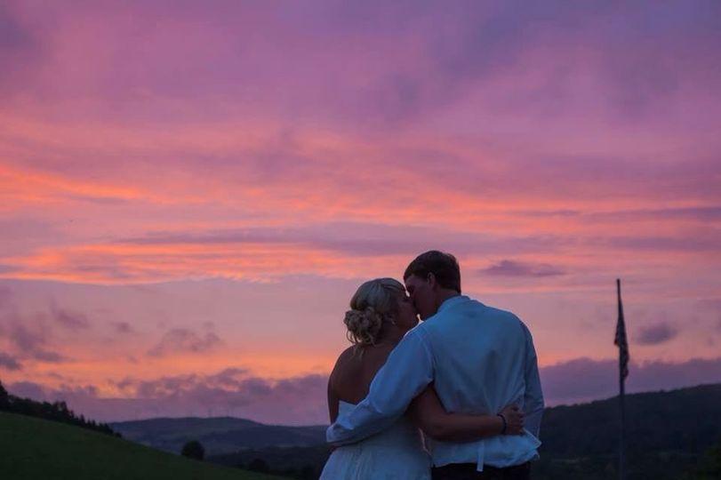 Newlyweds kissing at sunset