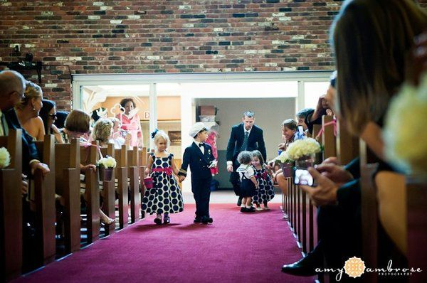 The flower girl dresses were navy polka dot accented with hot pink. They carried tin buckets with...