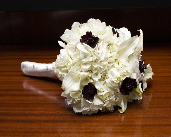 Chocolate cosmos, white calla lillies, and white hydrangeas accented with bouquet jewels