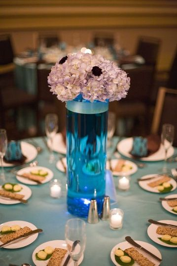 Blue hydrangeas and chocolate cosmos in cylinder vase filled with aquamarine color water