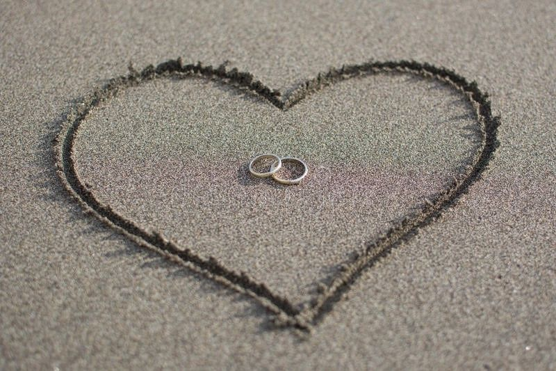 Heart and wedding rings in sand