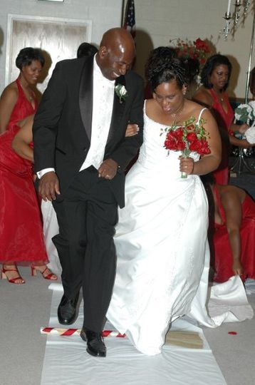 The O'Neal's start their lives together by jumping a broom decorated in their wedding colors of red...