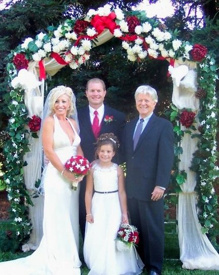 Group photo by the wedding arch