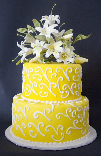 Cake covered in yellow fondant and royal icing swirls and gumpaste flowers on top.