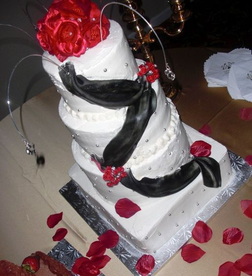 Buttercream covered cake with black fondant swag, red silk flowers and decorative cake jewelry...
