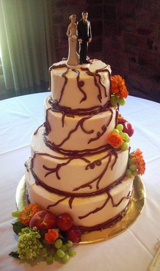 Vines, fruit and flowers.  Buttercream covered cake with fresh fruit and flowers.