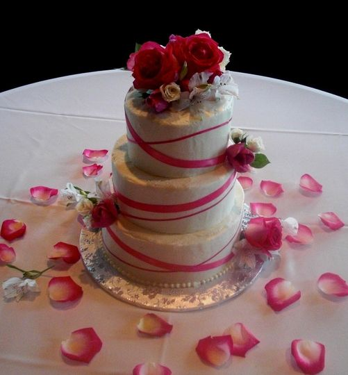 Buttercream covered cake with simple fuchsia ribbon and fresh flowers for decoration.
