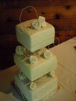 3 square tiers with acrylic riser cubes. Gumpaste roses all in shades of white with spun sugar to...