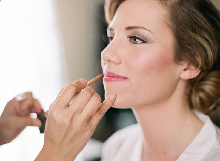 Bride putting on lip liner