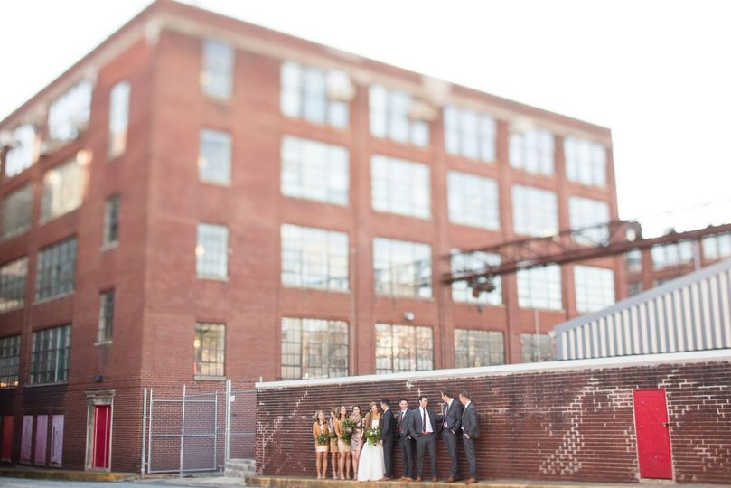 Newlyweds and their guests by the brick wall