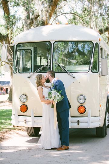 Newlyweds kissing in front of the cream vintage VW Bus