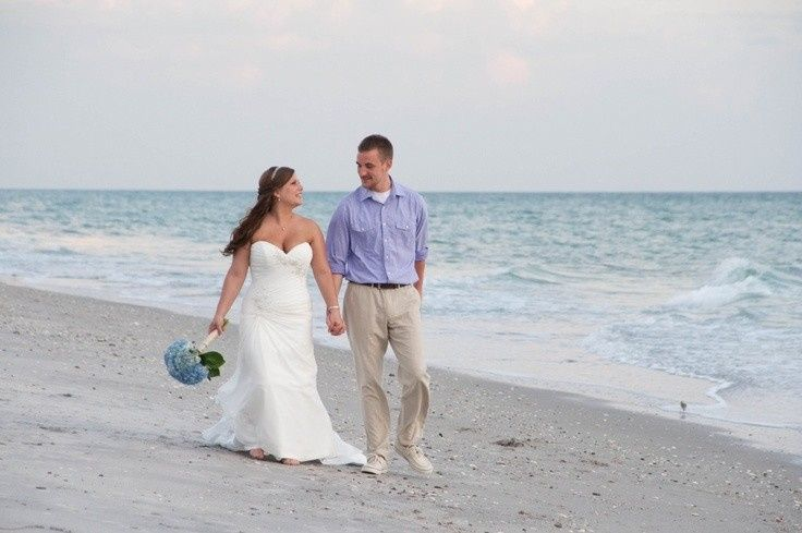 Bride and groom walking along the shore