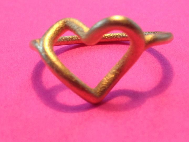 Infinite Love Ring in Matte Gold: A heart from the front, an infinity from the top. The shadow...
