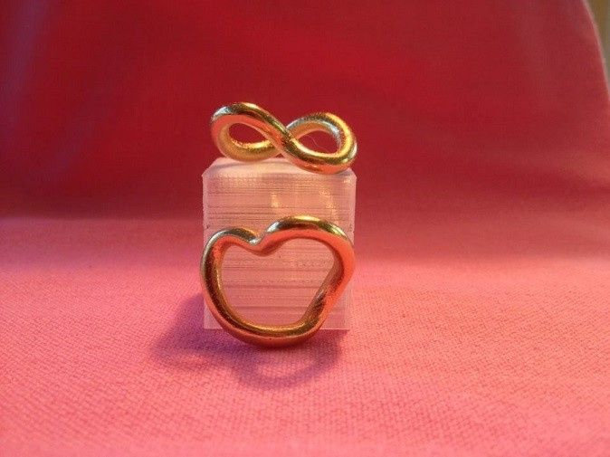 "Infinite Love Pendents in gold: A heart from the front, an infinity from the top. (1"" diameter)..."