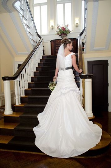 Bride showcasing dress by the stairs