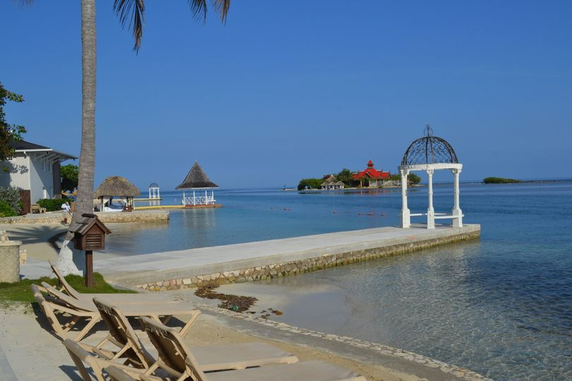 Beach area of Sandals Royal Caribbean with the Royal Thai restaurant and the private island in the...
