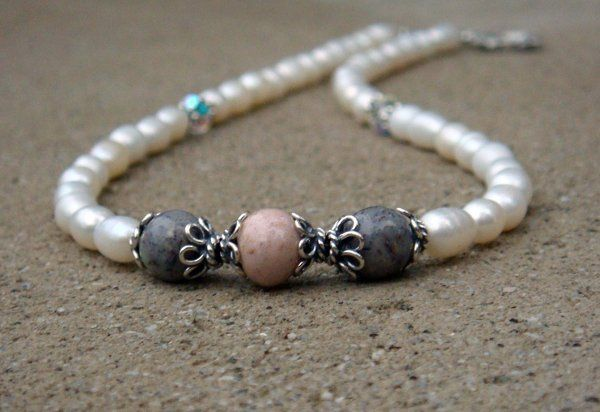 Floral keepsake beads are the focal point of the freshwater pearl necklace.