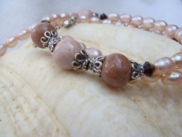 Handmade flower petal beads are the focal point of this freshwater pearl necklace.