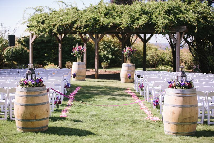 Ceremony in front of wisteria covered arbor.
