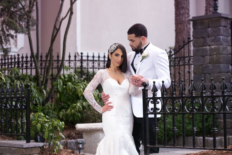 lightmaster studios bride and groom by wrought iron gate lace sheath wedding dress and white tuxedo jackets westmount country woodland park nj 2019 51 537014 v2