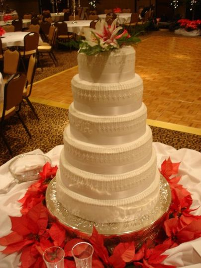 Tiered buttercream cake with pearlized accents and monogram.