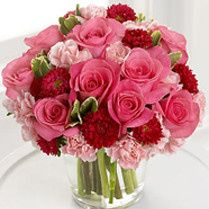 Centerpiece of roses and carnations with accents of variegated pittispourum
