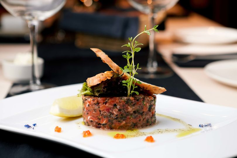 Elegantly plated steak tartare topped with housemade crostini and seasonal microgreens.