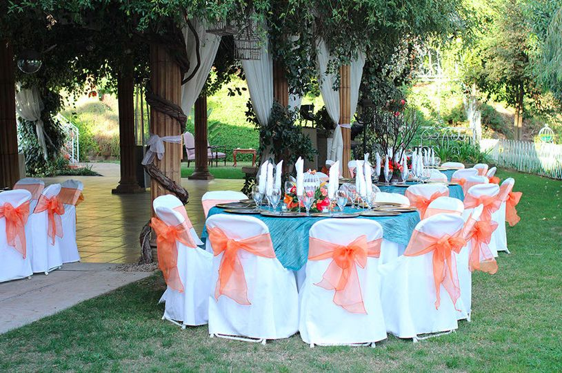 Chair tied with orange ribbon and table topped with aqua linen