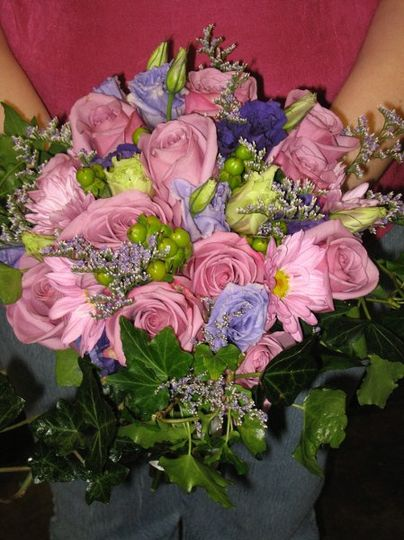 Cool Water roses, purple, green and lavender lisianthus, green hypericum, caspia and ivy help make...