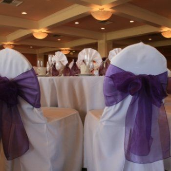 Beautiful white chair covers with Regal Purple bows in a country club setting.