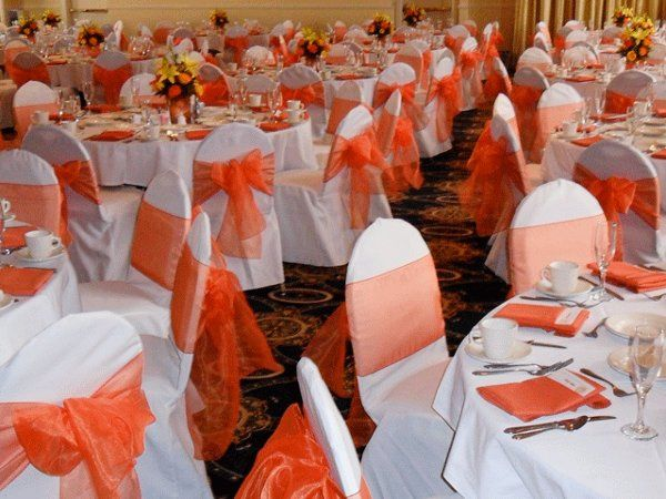 White chair covers with Orange organza bows.