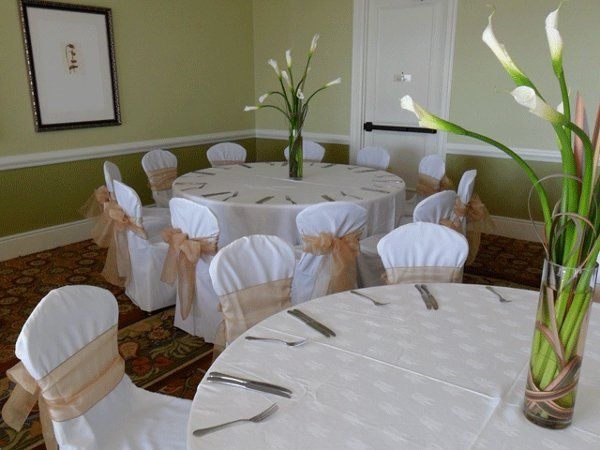 White chair covers with gold organza bows.