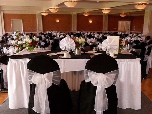Black chair covers with White organza bows. Head table