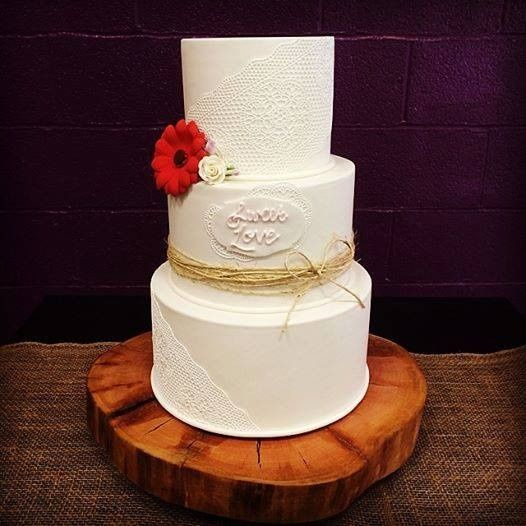 White wedding cake with a red flower