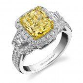 Yellow diamond engagement ring surrounded by white diamonds in 18 karat white gold.