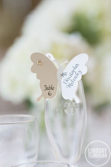 Butterflies at the top of champagne glasses for escort cards...