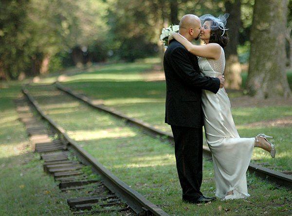Bride and Groom kissing on railroad tracks.